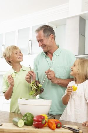 5 10 year old girl: Grandchildren Helping Grandfather To Prepare Salad In Modern Kitchen