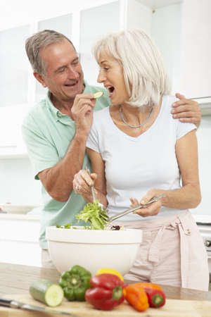 Senior Couple Preparing Salad In Modern Kitchen photo