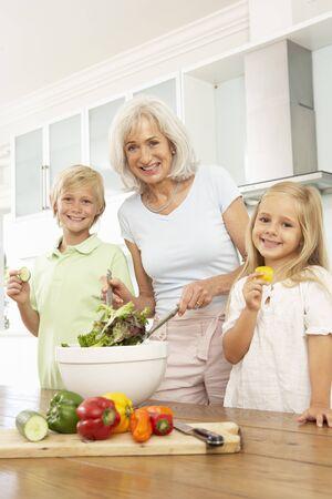 Grandchildren Helping Grandmother To Prepare Salad In Modern Kitchen Stock Photo - 8198676