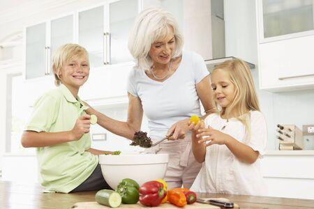 5 10 year old girl: Grandchildren Helping Grandmother To Prepare Salad In Modern Kitchen Stock Photo