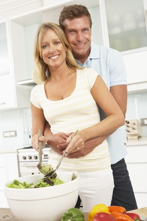 Couple Preparing Salad In Modern Kitchen photo