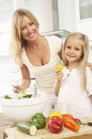 mother daughter: Hija & de madre, preparar la ensalada en la cocina moderna Foto de archivo