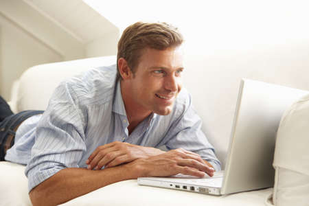 Man Using Laptop Relaxing Sitting On Sofa At Home Stock Photo - 8198739
