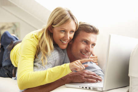 Couple Using Laptop Relaxing Sitting On Sofa At Home Stock Photo - 8198758