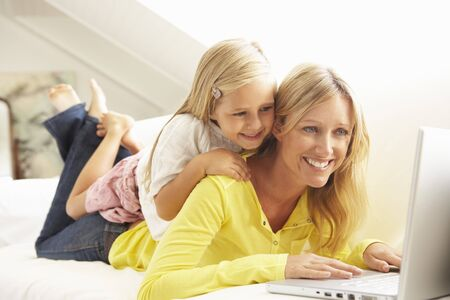 Mother And Daughter Using Laptop Relaxing Sitting On Sofa At Home photo