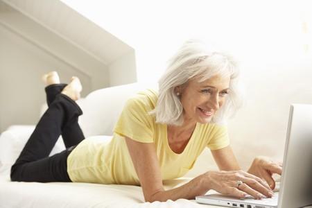 senior ordinateur: Senior femme utilisant portable relaxant assis sur le Sofa � domicile