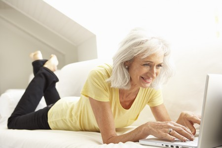 Senior Woman Using Laptop Relaxing Sitting On Sofa At Home photo