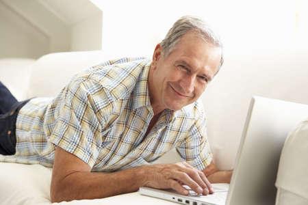 Senior Man Using Laptop Relaxing Sitting On Sofa At Home Stock Photo - 8198774