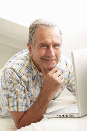 Senior Man Using Laptop Relaxing Sitting On Sofa At Home Stock Photo - 8198703