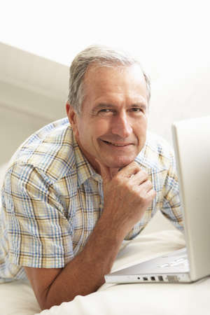 Senior Man Using Laptop Relaxing Sitting On Sofa At Home Stock Photo - 8198703