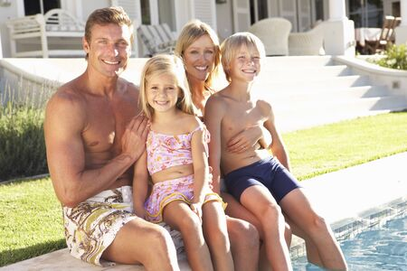 Family Outside Relaxing By Swimming Pool photo