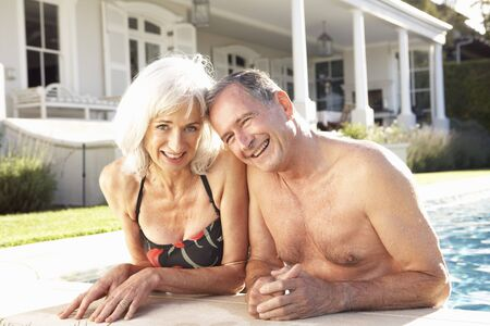 Senior Couple Relaxing by Outdoor Pool photo