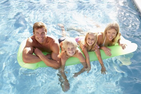 Family Outside Relaxing In Swimming Pool photo