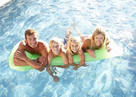 lilo: Family Outside Relaxing In Swimming Pool Stock Photo