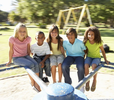 playground ride: Group Of Children Riding On Roundabout In Playground