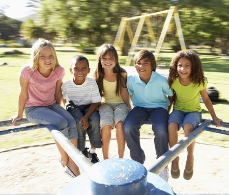 roundabout: Group Of Children Riding On Roundabout In Playground