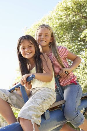 see saw: Two Girls Riding On See Saw In Playground Stock Photo