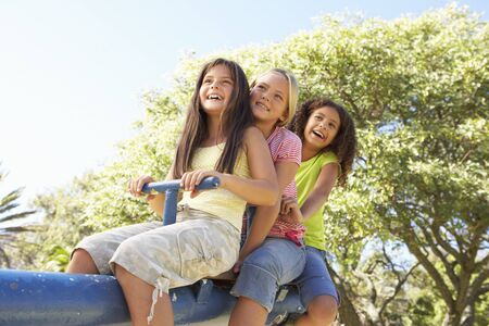 see saw: Three Girls Riding On See Saw In Playground Stock Photo