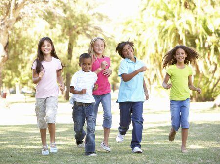 Group Of Children Running Through Park