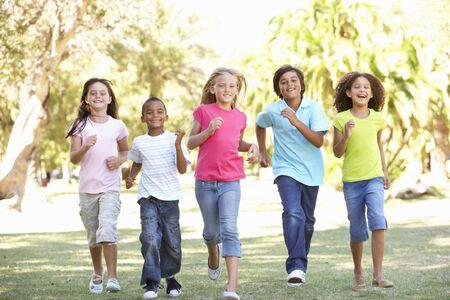 male child: Group Of Children Running Through Park