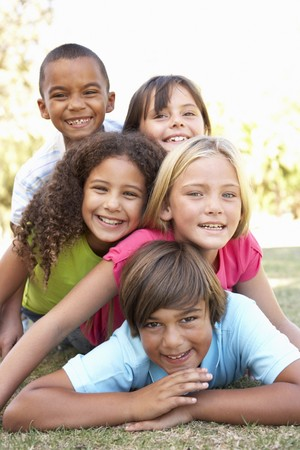 children playing outside: Group Of Children Piled Up In Park Stock Photo