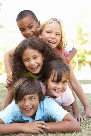 Group Of Children Piled Up In Park Stock Photo - 8198819