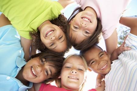 niños jugando en el parque: Grupo de niños Looking Down en cámara  Foto de archivo