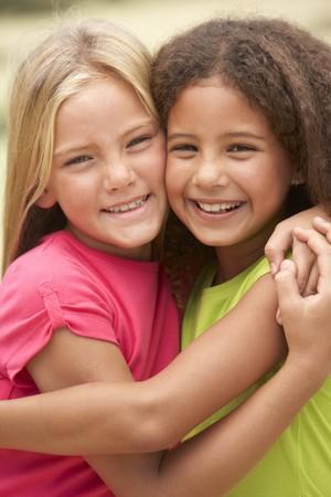 mejores amigas: Dos ni�as en Parque Giving entre s� Hug