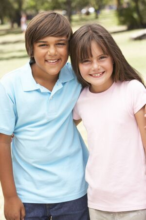 9 year old girl: Two Children In Park Giving Each Other Hug Stock Photo