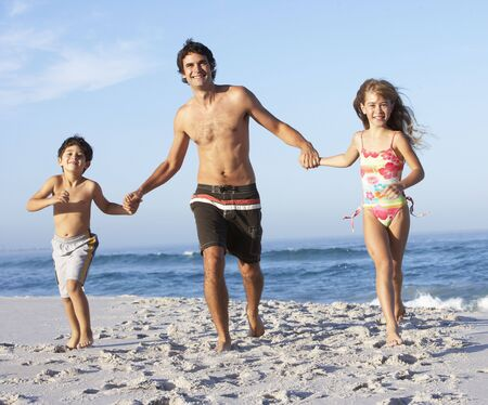 Father Running With Children Along Sandy Beach photo