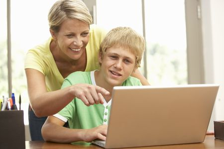 Mother And Teenage Son Using Laptop At Home photo