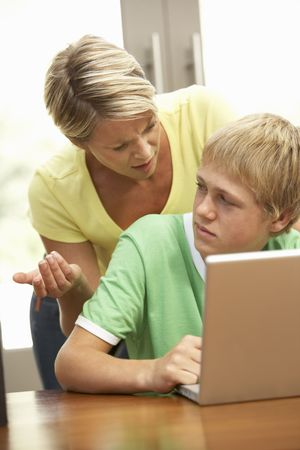 mom and son: Angry Mother And Teenage Son Using Laptop At Home Stock Photo