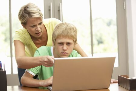 angry teenager: Angry Mother And Teenage Son Using Laptop At Home Stock Photo