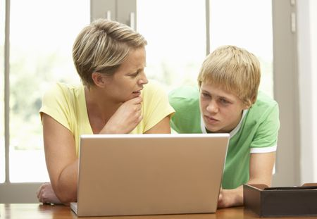 parent and teenager: Mother And Teenage Son Using Laptop At Home