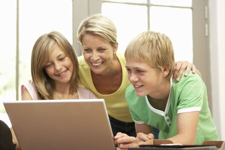 Mother And Teenage Children Using Laptop At Home photo