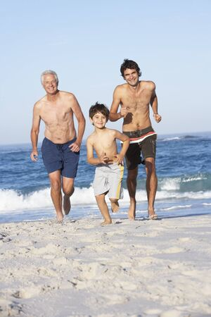 Grandfather, Father and Grandson Running Along Beach Stock Photo - 8482978