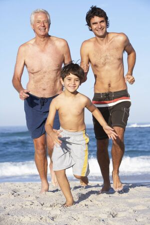 three generation: Grandfather, Father and Grandson Running Along Beach