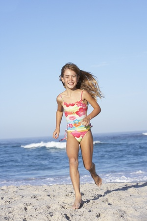 7 year old girl: Young Girl Running Along Sandy Beach Stock Photo
