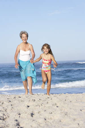 Grandmother Running With Granddaughter Along Sandy Beach Stock Photo - 8483018