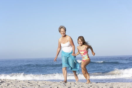 granddaughters: Grandmother Running With Granddaughter Along Sandy Beach