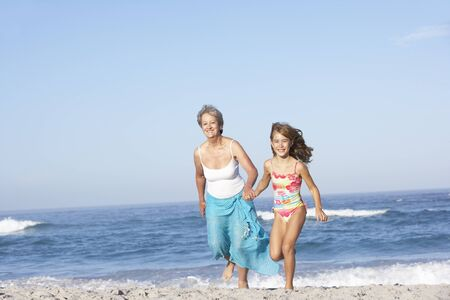 Grandmother Running With Granddaughter Along Sandy Beach photo