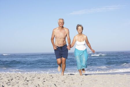 board shorts: Senior Couple On Holiday Running Along Sandy Beach Stock Photo