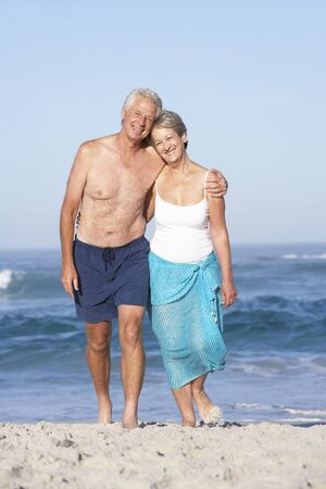 Senior Couple On Holiday Walking Along Sandy Beach photo