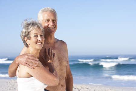 board shorts: Senior Couple On Holiday Walking Along Sandy Beach Stock Photo