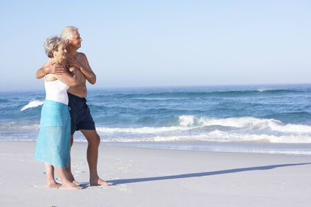 ancianos caminando: Pareja Senior en vacaciones caminando a lo largo de la playa de Sandy