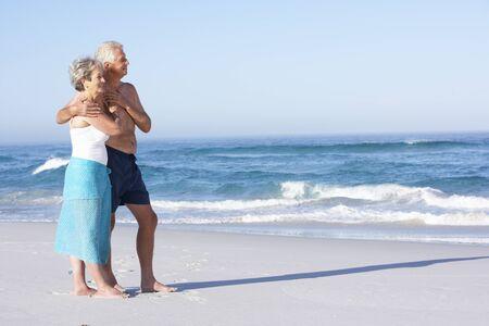 senioren wandelen: Senior koppel op vakantie wandelen langs zand strand Stockfoto
