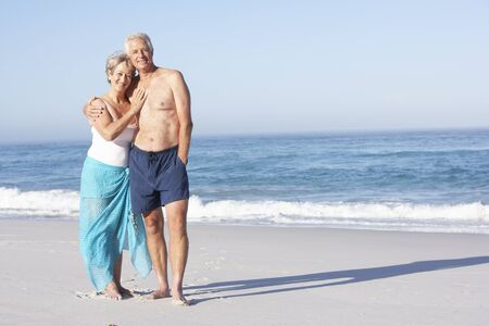 Senior Couple On Holiday Walking Along Sandy Beach Stock Photo - 8483128