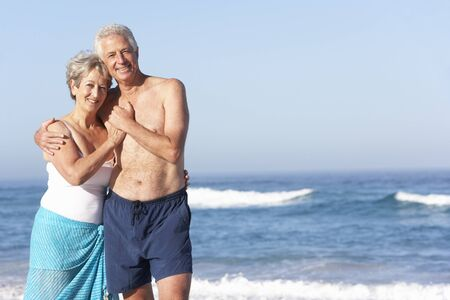 Senior Couple On Holiday Walking Along Sandy Beach photo