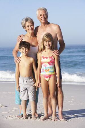 grandddaughter: Grandparents And Grandchildren Standing On Sandy Beach Stock Photo