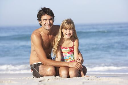 Father And Daughter Wearing Swimwear Sitting On Sandy Beach photo